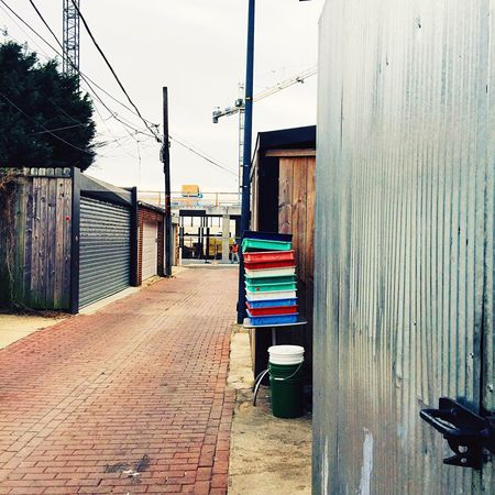 Alley ways can lead to discoveries! Alley Alleyway Trays Color Brick Road Buckets Garages Cranes Wood Shed Construction Urban Streetphotography IPhoneography Patterns Patterns & Textures