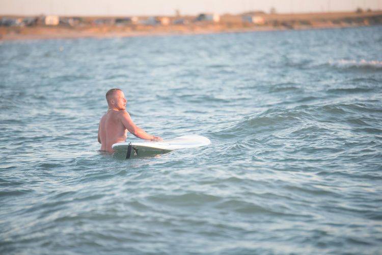 Rear view of shirtless male surfer with surfboard in sea