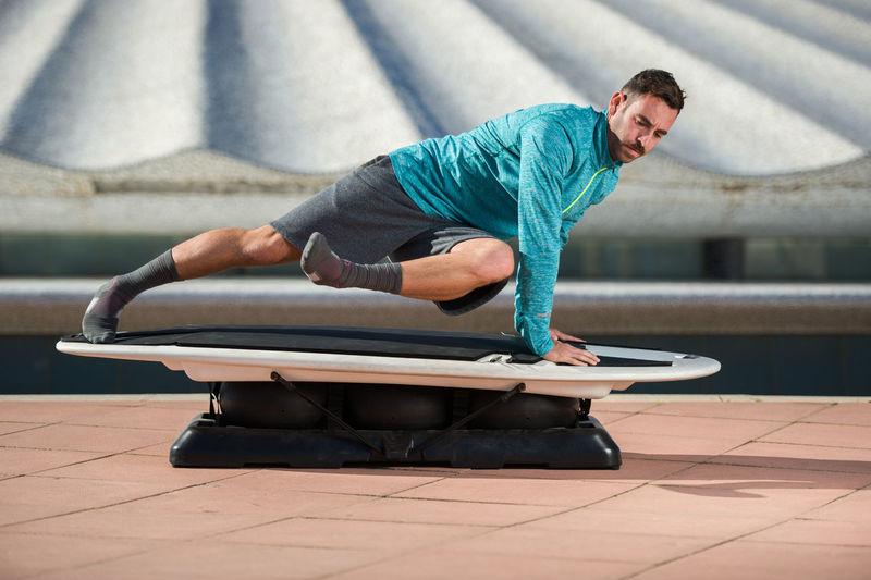 man practicing surf movements Lifestyle Man Practice Surf Movement Park Sports Training Workout
