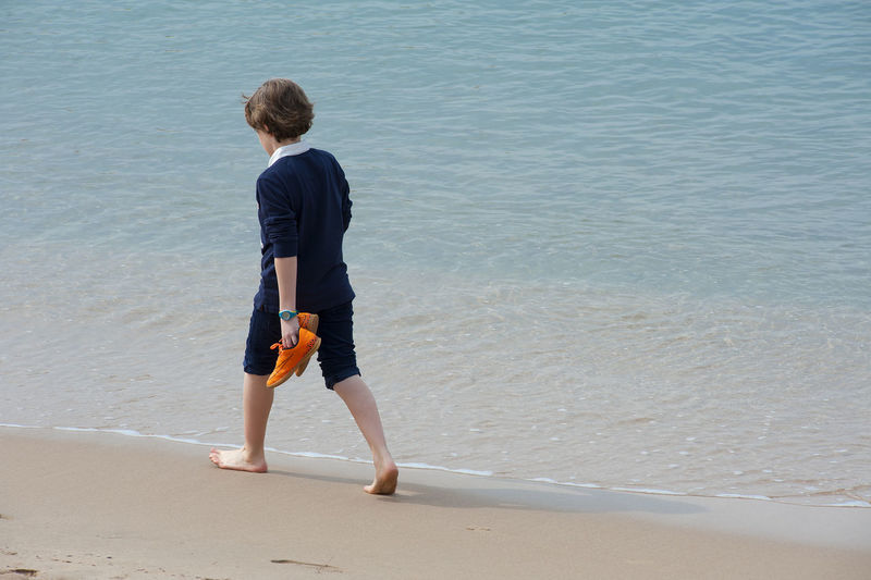 Beach Casual Clothing Coastline Day Full Length Idyllic Leisure Activity Lifestyles Melancholy Orange Shoes Outdoors Remote Sad Sadness Sand Scenics Sea Shore Solitude Tourism Tranquility Vacations Water Wave