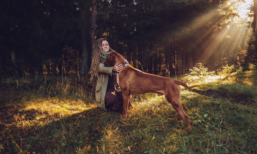 Young smiling woman with dreadlocks in autumn fall forest in the morning sunshine playing with a dog ridgeback Plant Domestic Animals Animal Mammal Domestic Land Animal Themes Pets One Animal Real People One Person Tree Grass Field Full Length Vertebrate Nature Lifestyles Livestock Young Adult Lens Flare Outdoors Riding Herbivorous Dreadlocks Ridgeback