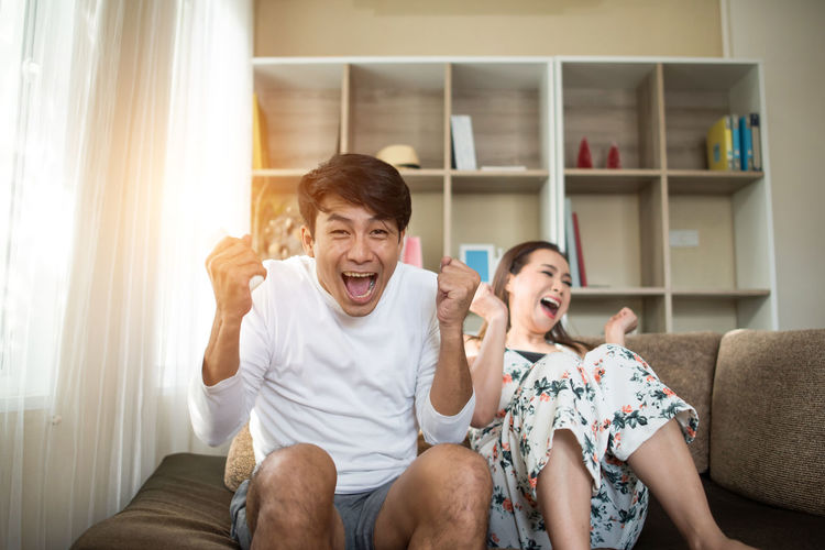 Happy couple clenching fists while watching tv on sofa at home