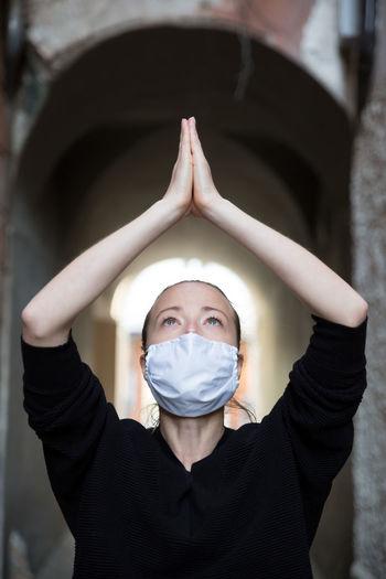 Close-up of woman wearing flu mask meditating outdoors