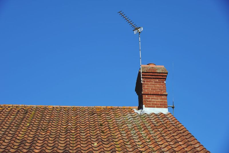 view of chimney with antenna in english styke of building Architecture Built Structure Sky Low Angle View Clear Sky Building Exterior Building Blue Roof Copy Space Roof Tile Day Tower Place Of Worship Chimney Outdoors Religion No People Nature Sunlight