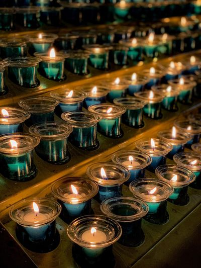 High angle view of lit candles on table in church