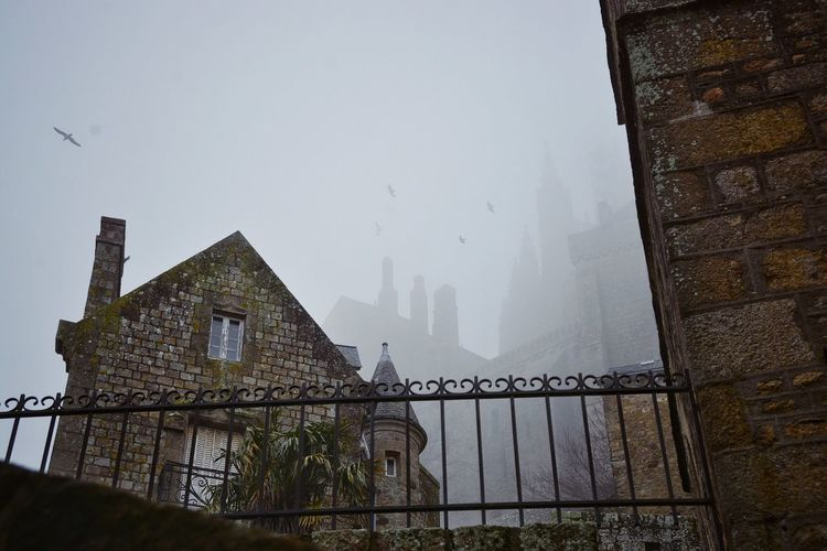 Low angle view of castle during foggy weather
