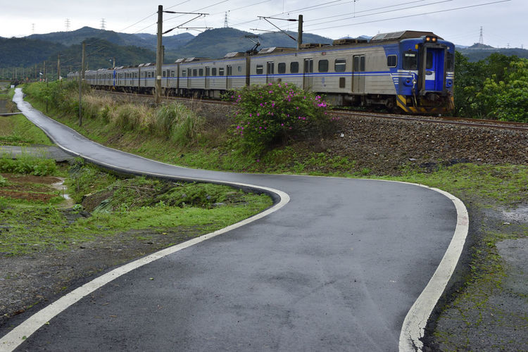 Travel on a railway, after a holiday in the country. Bending Travel Architecture Building Exterior Built Structure Curve Curved Road Day Direction Grass Land Vehicle Mode Of Transportation Nature No People Outdoors Plant Public Transportation Rail Transportation Road Sky Track Train Train - Vehicle Transportation Vacation