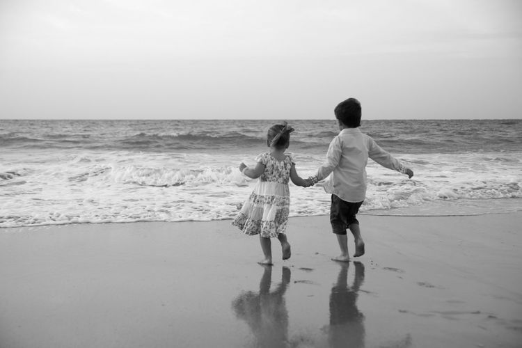 Ankle Deep In Water Beach Bonding Boys Childhood Day Full Length Horizon Over Water Leisure Activity Lifestyles Nature Outdoors Real People Rear View Sand Scenics Sea Shore Sky Standing Togetherness Two People Vacations Walking Water