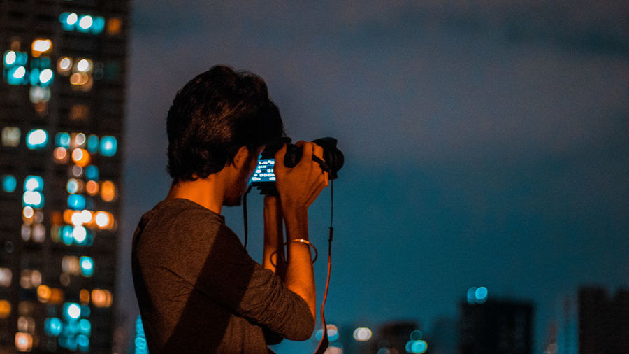 Teenage Boy Photographing With Camera In City At Night