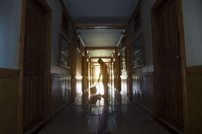Woman working on a floor . Cleaning Home Missions Room Silhouette Walk Working Accommodation Besom Broom Building Floor Hotel Room Housemaid Indoors  Lifestyles Light And Shadow Maid One Person People Real People Scuffs Swab Sweeping Women