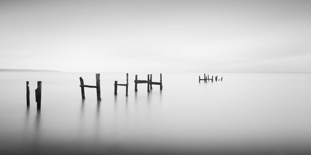 Still Standing - Atmospheric Mood Black And White Copy Space Decay And Dereliction Distant Horizon Over Water Outdoors Pier Scenics Sea Shore Tranquil Scene Tranquility Water Wood Structure Landscapes With WhiteWall The Great Outdoors With Adobe