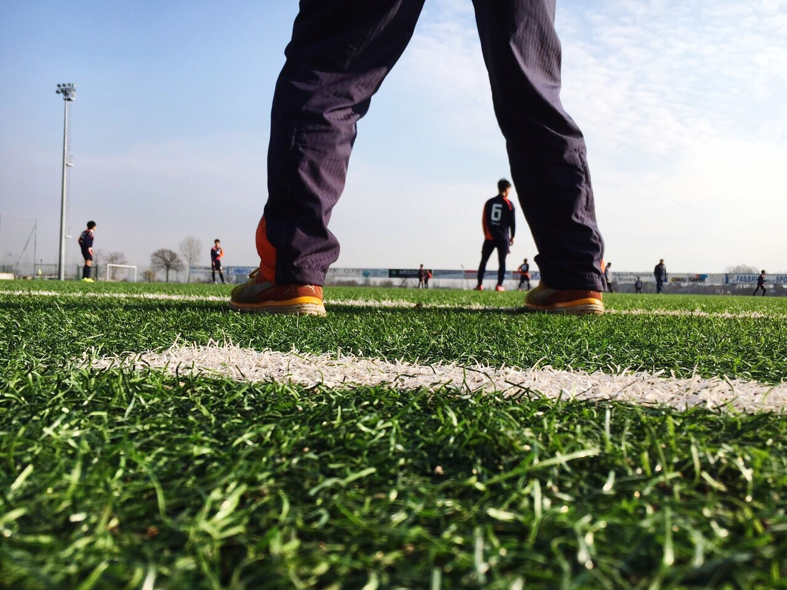 low section, person, grass, lifestyles, men, leisure activity, human foot, surface level, shoe, lawn, green color, group of people, field, day, outdoors, green, sportswear, tourism, the way forward