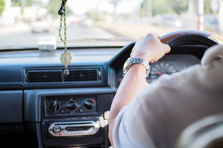Cropped image of man driving car