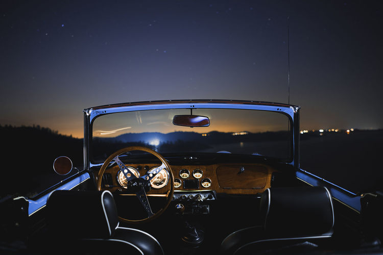 Illuminated vintage car against sky at night