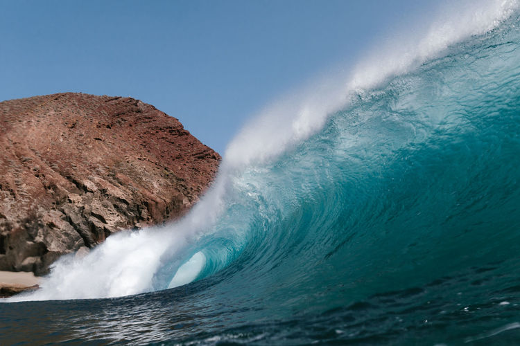 Blue wave breaking front a red mountain in tenerife