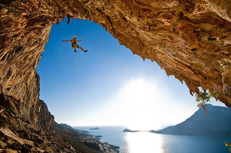 Low angle view of man climbing rock by lake against sky