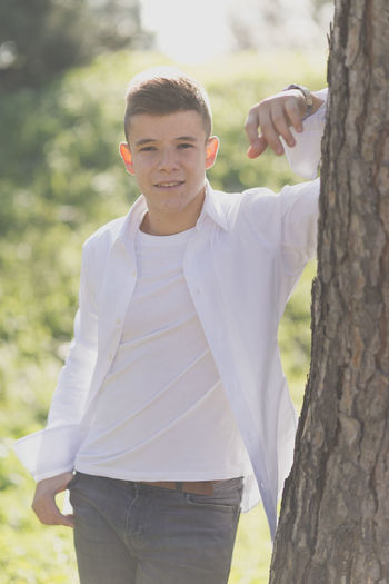 Portrait of a stylish young teenager in the city Tree Tree Trunk Looking At Camera Day Trunk Casual Clothing Young Men Standing Young Adult One Person Three Quarter Length Plant Portrait Leisure Activity Smiling Nature Lifestyles Front View Outdoors Teenager