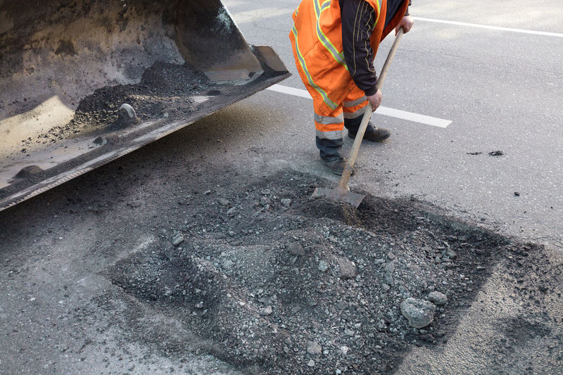 Low section of man digging on road