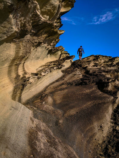 Low angle view of man climbing on rock against sky