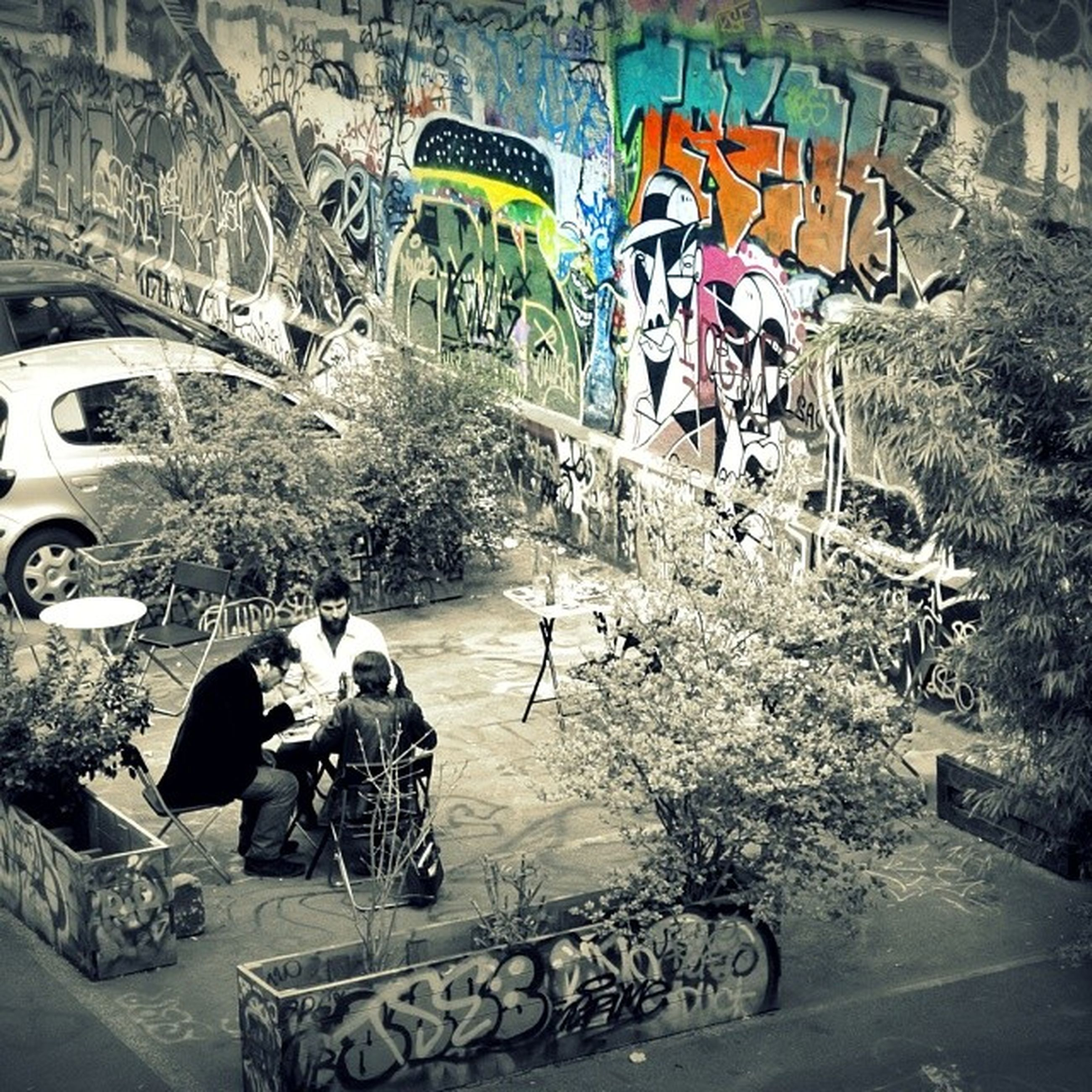 graffiti, street, land vehicle, built structure, high angle view, architecture, building exterior, car, transportation, road, art and craft, art, wall - building feature, creativity, mode of transport, multi colored, day, outdoors, tree, city