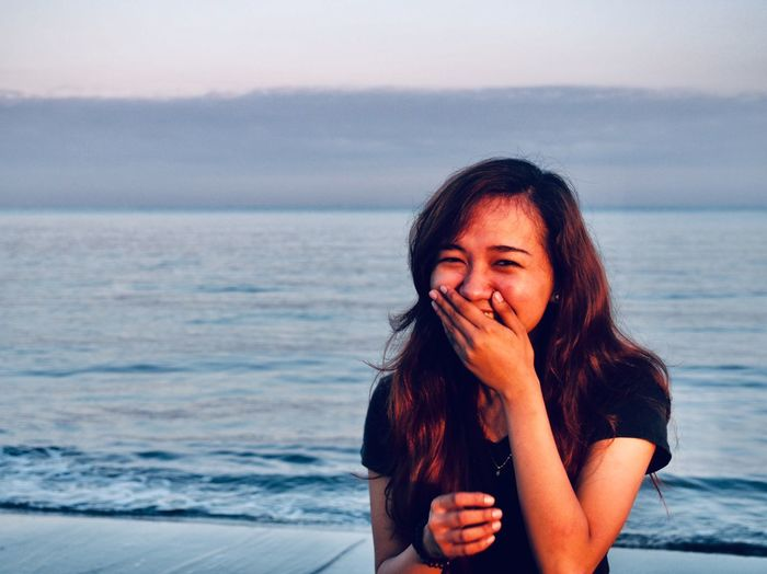 Portrait of beautiful young woman laughing at beach against sky during sunset