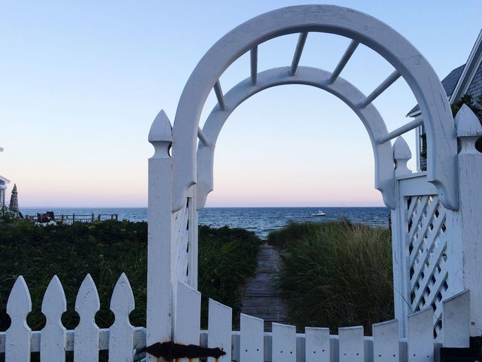 Sea seen through arch fence against sky during sunset