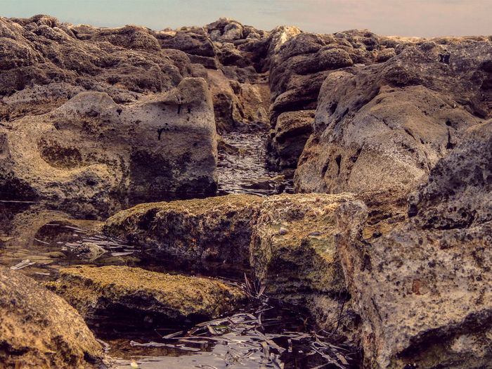 Low angle view of rocks at beach against sky