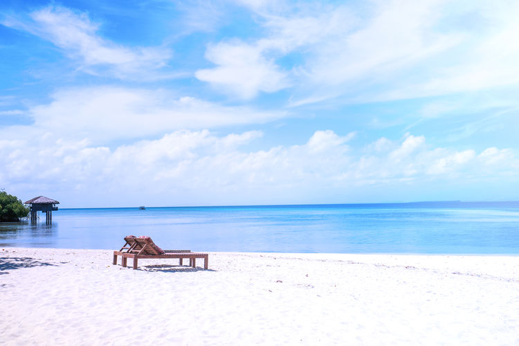 Empty lounge chairs at beach against sky