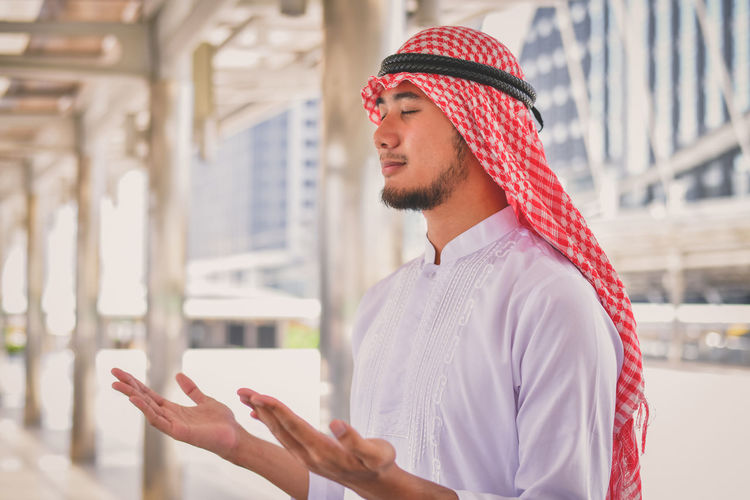 Handsome young man praying while standing on elevated road