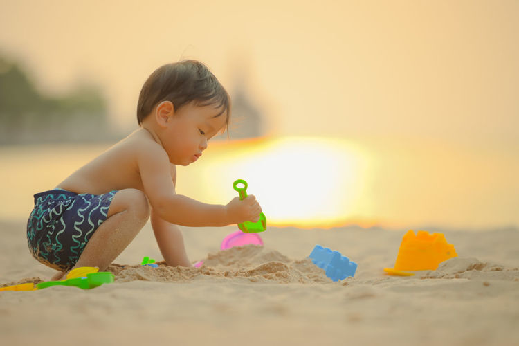 Cute boy playing with toy on beach