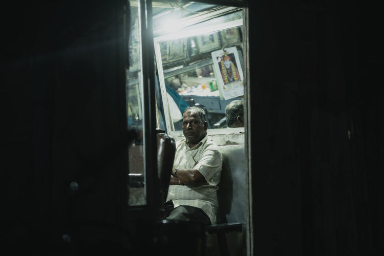 Man sitting in bus window at home