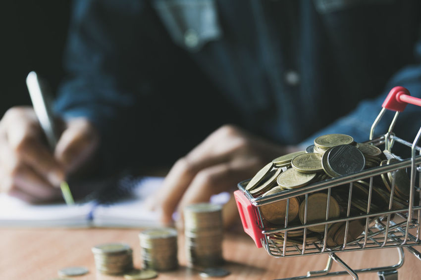 Hand writing and pile of coin in the shopping cart for accounting and business concept. One Person Midsection Real People Table Human Hand Holding Finance Men Indoors  Selective Focus Focus On Foreground Business Hand Working Occupation Day Container Coin Close-up