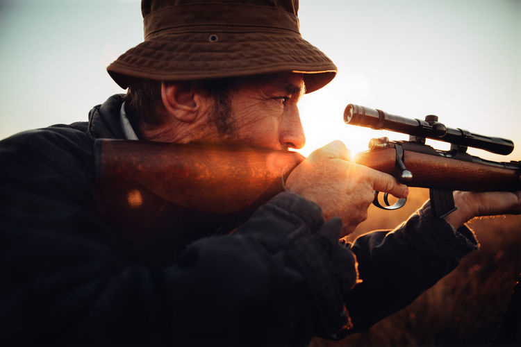 Agriculture Field Gun Headshot Hunter Hunting Leisure Activity Lifestyle Man Mature Meat Nature Outdoors People Pointing Prey Rural Scene Skill  Sniper Sunbeam Sunflare Sunrise Weapon