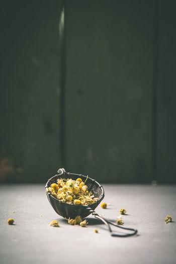 Herbs in tea strainer on table