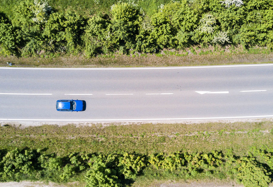 street with car - aerial view Car Day Environment Field Green Color Growth Land Land Vehicle Landscape Marking Mode Of Transportation Motor Vehicle Nature No People Outdoors Plant Road Road Marking Symbol Transportation Tree