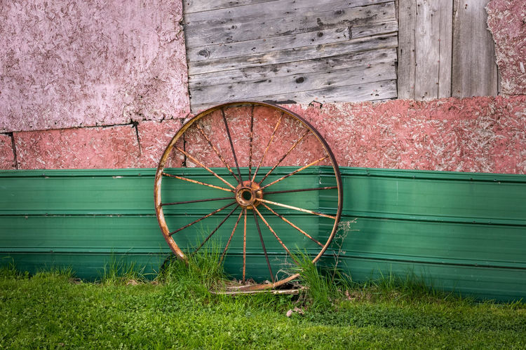 Abandoned wheel on field against wall