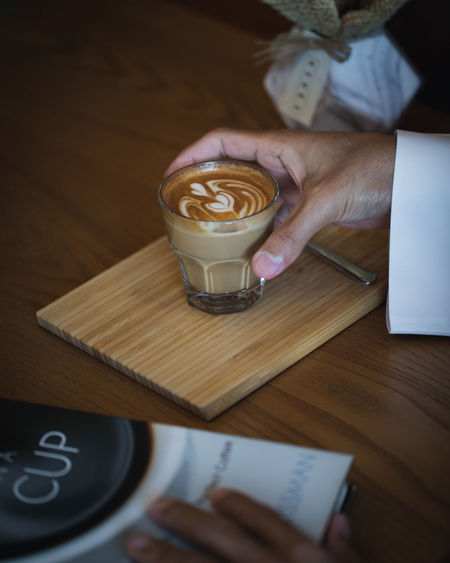 Coffee on Wooden Table with Book in Cafe Ijas Muhammed Photography Human Hand Drink Food And Drink Hand Coffee - Drink Coffee One Person Refreshment Table Human Body Part Coffee Cup Indoors  Mug Holding Real People Cup Lifestyles Wood - Material Adult Hot Drink Latte Frothy Drink Glass