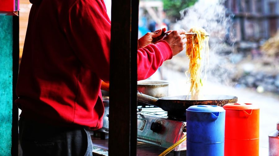 Midsection of man preparing noodles at concession stand on roadside in city