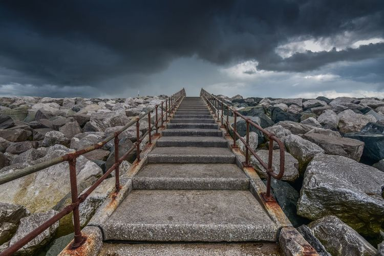 Staircase Amidst Rocks Against Cloudy Sky