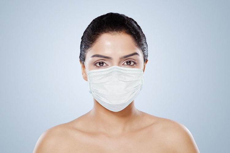 Portrait of beautiful woman wearing mask against colored background