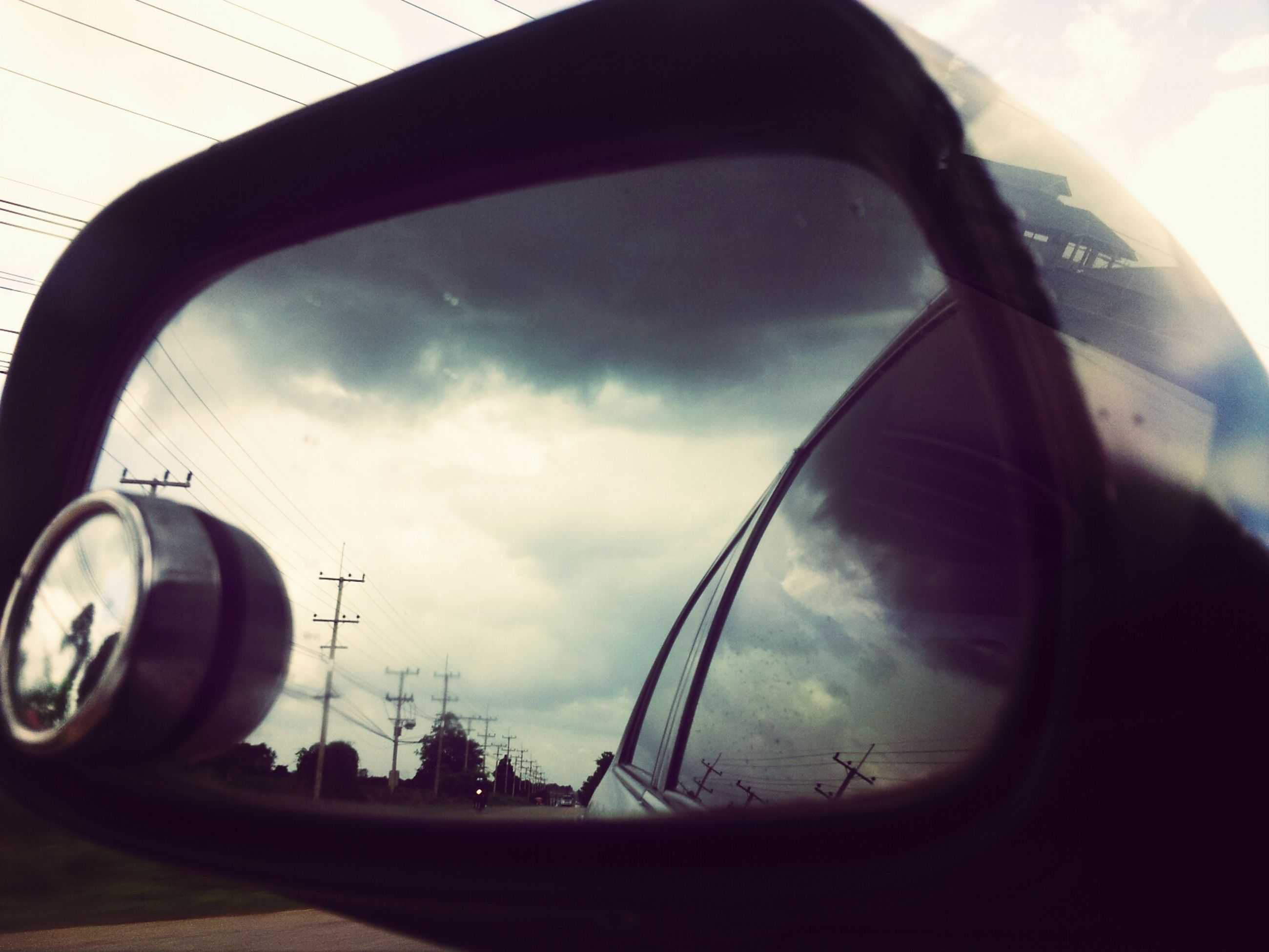 transportation, mode of transport, land vehicle, car, sky, vehicle interior, air vehicle, side-view mirror, airplane, cloud - sky, glass - material, part of, reflection, road, vehicle part, street, travel, transparent, stationary, cropped