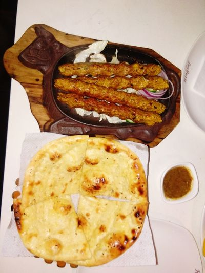 Northern Indian Cuisine Close-up Fresh From The Oven TangyLemon Sauce Appetizing  Chicken Kebab Garlic Butter Naan