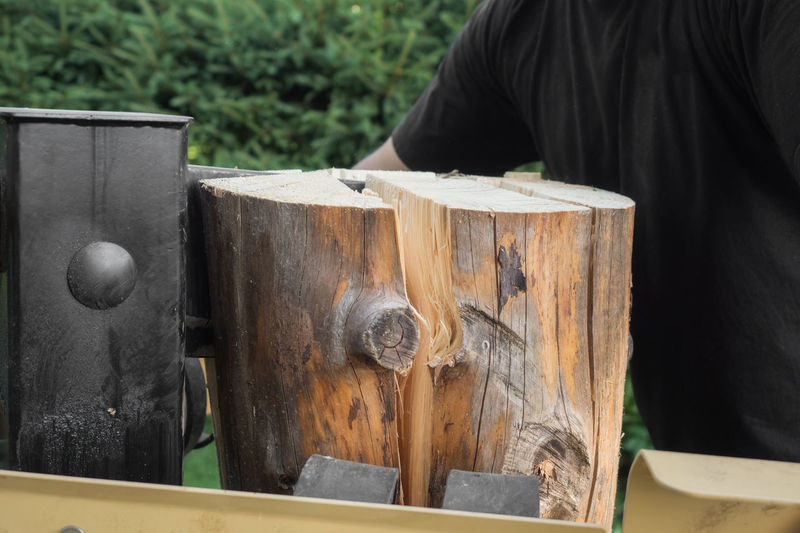 A firewood split with wooden splitter outdoor Machine Wood Worker Close-up Day Firewood Focus On Foreground Garden Hydraulic Outdoors Real People Wood - Material