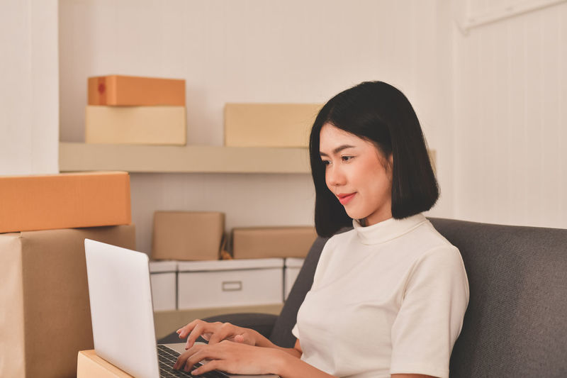 Adult Box Business Business Person Businesswoman Communication Computer Connection Hairstyle Indoors  Laptop Office One Person Sitting Smiling Technology Typing Using Laptop Waist Up Wireless Technology Women Young Adult