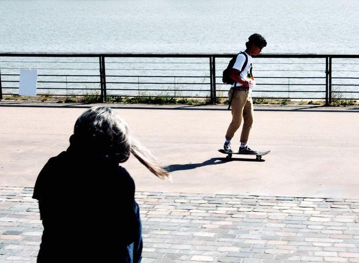 Full length of boy skateboarding on promenade in city during sunny day