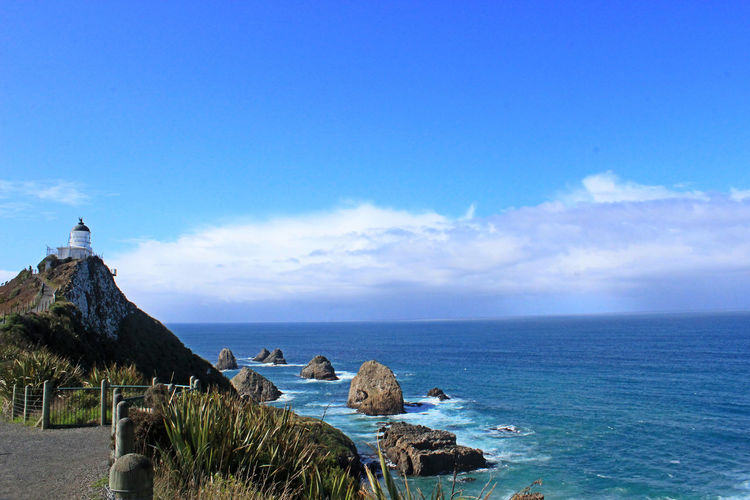 Nugget Point Lighthouse Nugget Point Beach Beauty In Nature Blue Cloud - Sky Copy Space Day Horizon Horizon Over Water Land Nature New Zealand No People Non-urban Scene Outdoors Rock Scenics - Nature Sea Sky Tranquil Scene Tranquility Water