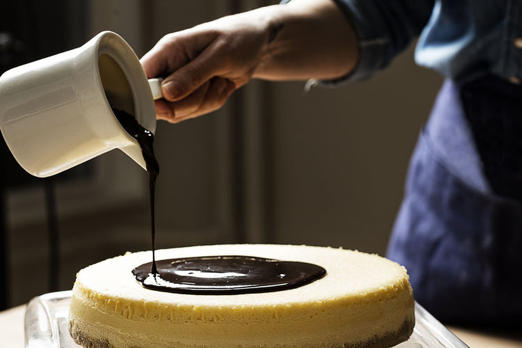 Midsection of person pouring chocolate sauce on cake