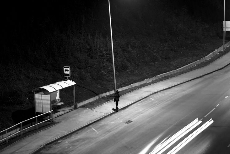 High angle view of silhouette woman walking on sidewalk by light trails at night