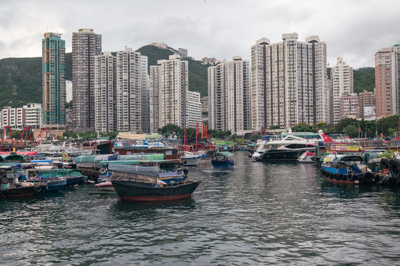 Boats moored in river by buildings in city against sky