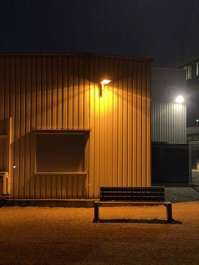 Empty bench against illuminated street light at night